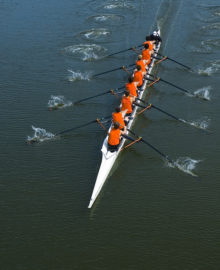 Full overhead image of an eight oar rowing crew in the open water. This is teamwork at its best.